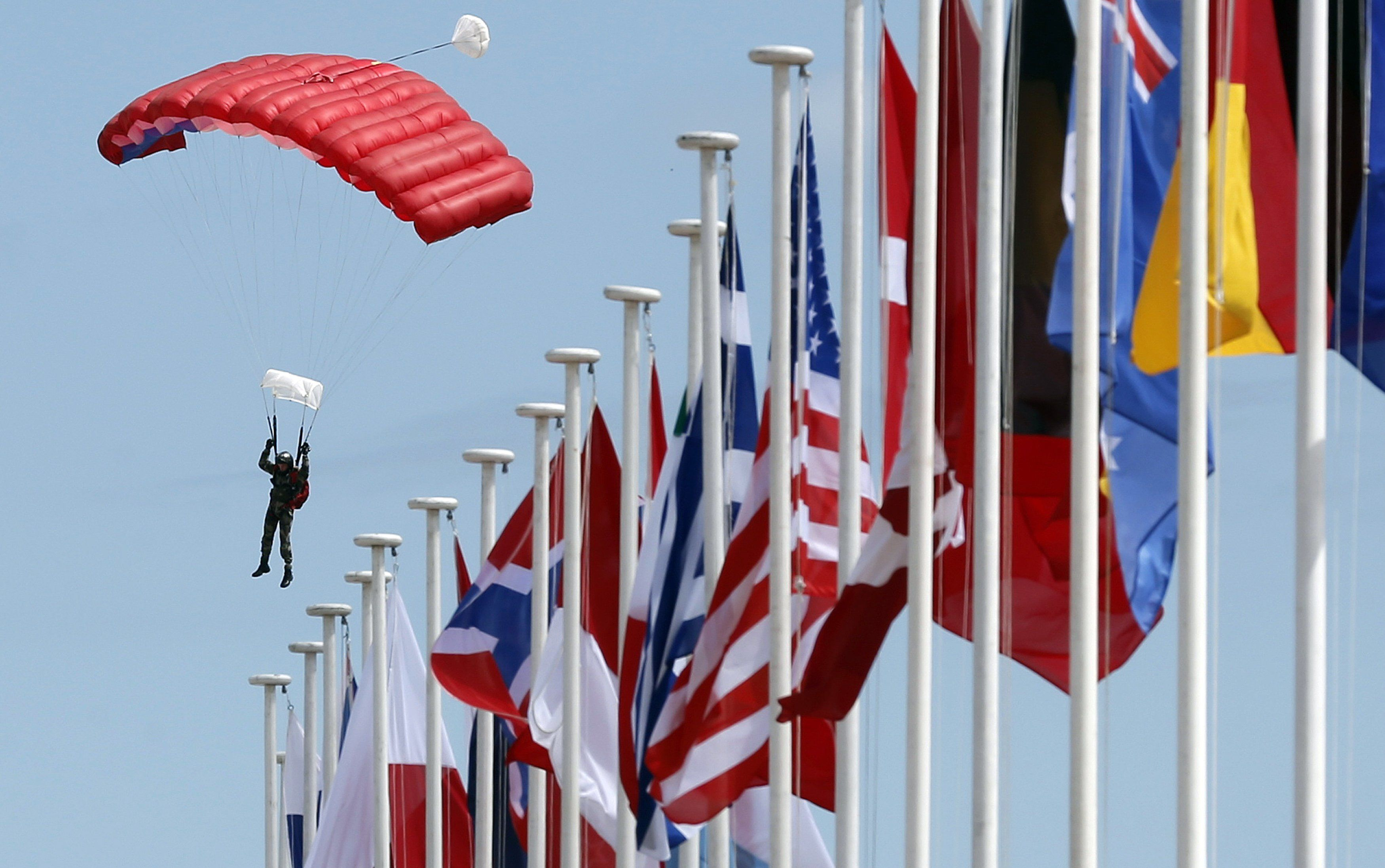 A paratrooper lands on Sword Beach near international flags during a D-Day celebration rehearsal in Ouistreham